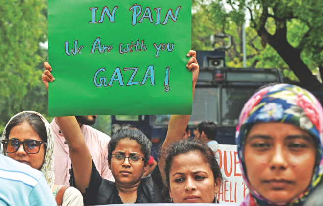 Indian protestors hold placards as they take part in a rally against Israeli attacks on Gaza in New Delhi, yesterday. Photo: AFP