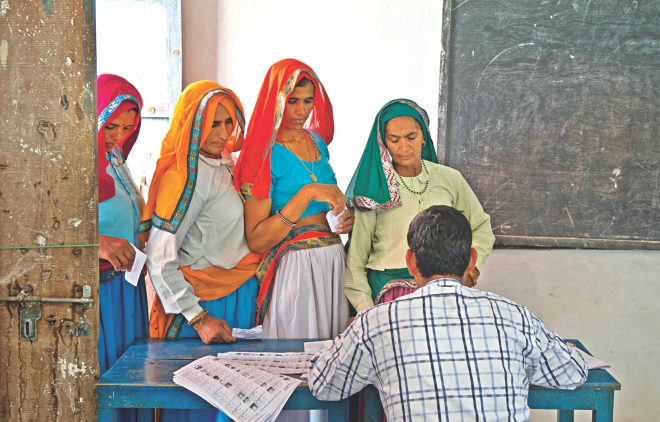 Indian women queue to cast their vote at a polling booth in Alwar. Photo: AFP