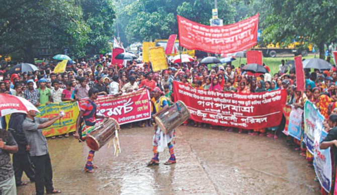 Indigenous people hold a gathering in front of the deputy commissioner's office in Chapainawabganj town yesterday demanding arrest and punishment of the land grabbers who raped a woman indigenous leader in Gomostapur upazila under Chapainawabganj district on August 4. They also reiterated their demand for formation of a separate land commission for the plain land indigenous people in different areas of the country.   PHOTO: STAR