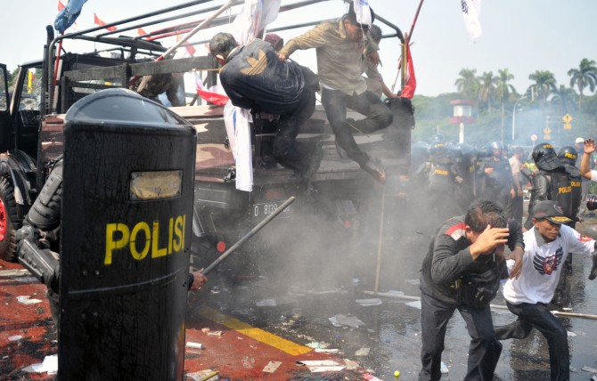 Indonesian anti-riot police move in to arrest supporters of presidential candidate Prabowo yesterday as they try to pass a blockade near the constitutional court in Jakarta.  Photo: AFP