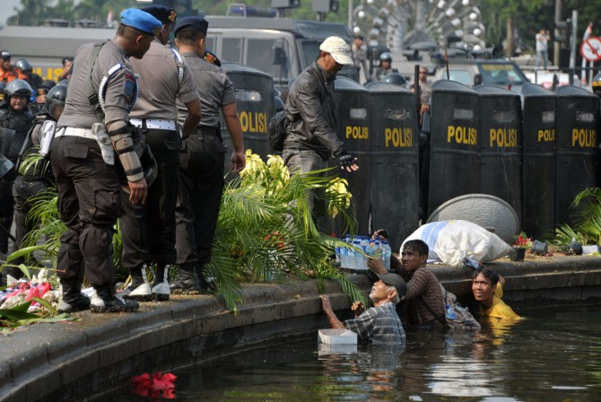 Street vendors hide in the water of a fountain during the clashes with police. Photo: AFP