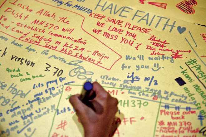 A man writes on a poster carrying messages for the passengers of the missing Malaysia Airlines plane at the Kuala Lumpur International Airport. Photo: AFP