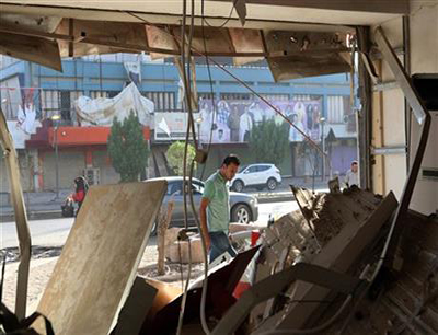 An Iraqi man inspects the site of a car bomb on Saadoun street in Baghdad, Iraq,  September. 5, 2014. The bomb exploded in a commercial area in central Baghdad on Tuesday night, killing and wounding civilians. Photo: AP