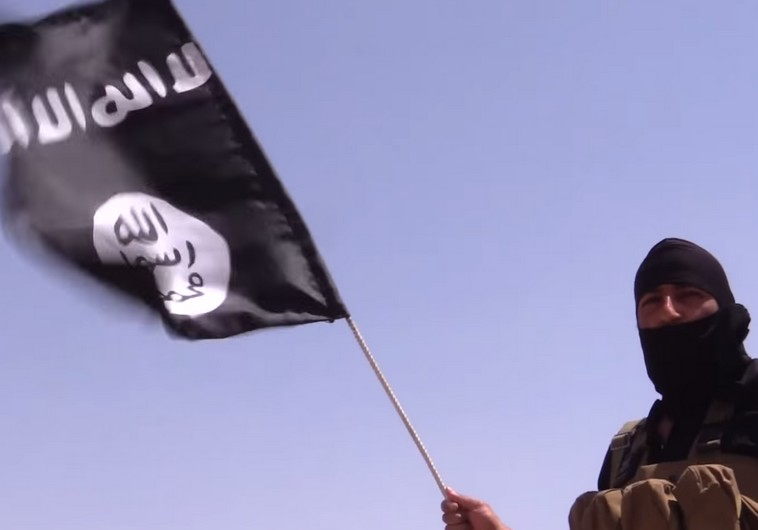 1.	An Islamic State member holds a flag with the group's insignia. Photo: Reuters