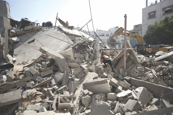 Palestinian Civil Defence workers search for survivors amidst the rubble of a building destroyed in an Israeli air strike, in Gaza City. Photo: AFP