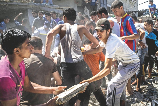 Palestinian men gather and remove the rubble of a house hit by an Israeli airstrike in the al-Shati refugee camp in Gaza City trying to look for survivors. Photo: AFP