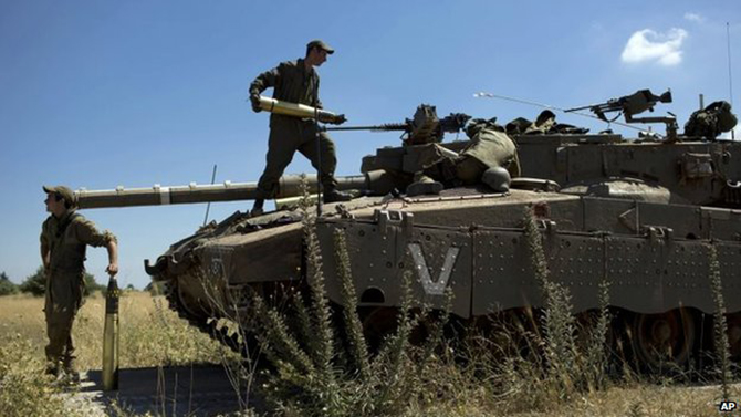 Israeli soldiers load shells in their tank in the Israeli-controlled Golan Heights, 22 June 2014 Israel said it attacked nine Syrian targets and direct hits were confirmed