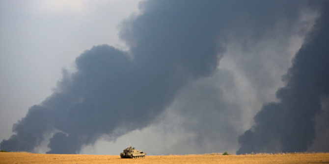 An Israeli tank sits in a field as heavy smoke rises from the Gaza Strip July 22. Photo: AP