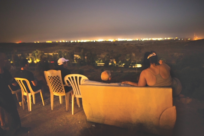 Israeli residents sit on a hill overlooking the Gaza Strip on Saturday to watch the fighting between the Israeli army and Palestinian militants. Photo: AFP
