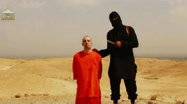 This image grabbed from a video posted on social media website shows a masked Islamic State militant speaks next to US journalist James Foley at an unknown location moments before beheading him.