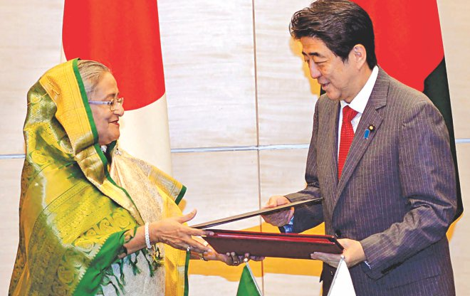 Prime Minister Sheikh Hasina and Japanese PM Shinzo Abe sign and exchange a joint statement at the latter's office in Tokyo yesterday. Photo: BSS