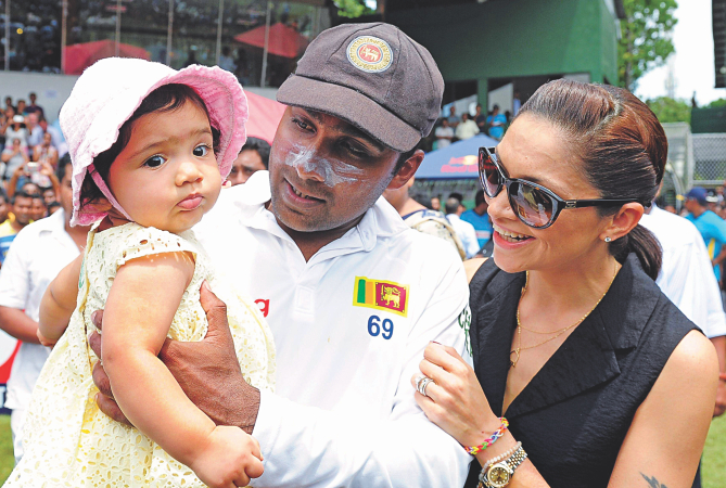Retiring Sri Lanka batsman Mahela Jayawardene holds his daughter Sansana as his wife Christina Sirisena looks on during the post-match ceremony at the Sinhalese Sports Club ground in Colombo yesterday.  PHOTO: AFP