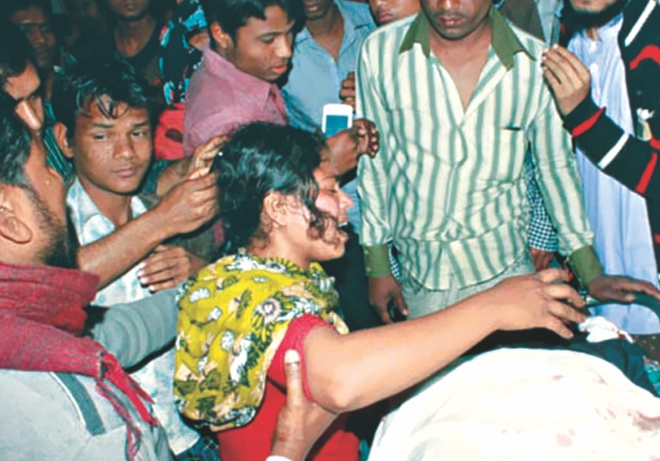 A family member cries over the body of a policeman killed when a prison van came under attack and three convicted JMB men were snatched at Trishal on Dhaka-Mymensingh highway yesterday. Photo: Banglar Chokh/Star