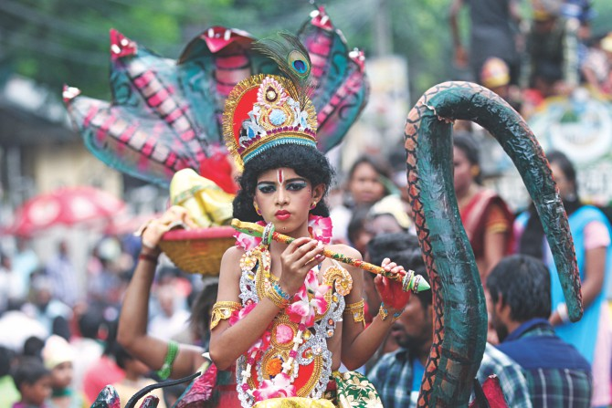 A boy dressed as Lord Krishna takes part in a procession on Janmashtami, a religious festival marking the birthday of the Hindu god, at Palashi intersection in the capital yesterday. Photo: Star