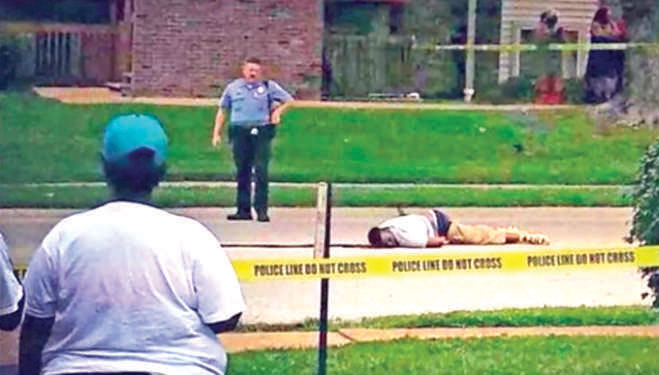A YouTube grab shows Michael Brown bleeding after being shot by Darren Wilson; a policeman looks on.