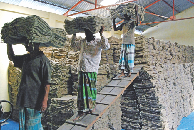 Workers arrange jute sacks in a store in Bogra. Use of bags made of jute to pack imported rice and wheat has been made mandatory. Photo: Star