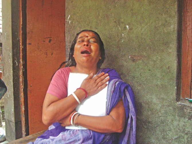 Kalpana Biswas, holding on tight to a photo of her daughter Trishna, cries her heart out at her residence in Jhenidah yesterday. Trishna was one of 11 people killed when a train rammed the bus they were travelling in at a level crossing on Friday.  Photo: Star