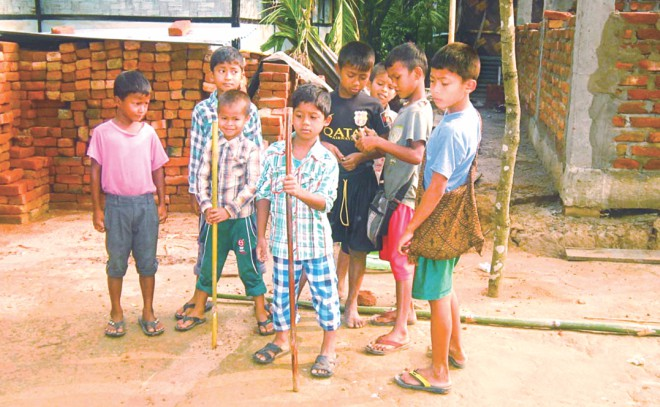 Even little kids, who refrain from classes in fear of attacks on the way to school yesterday, are forced to pick up sticks for self-preservation. Photo: Mintu Deshwara