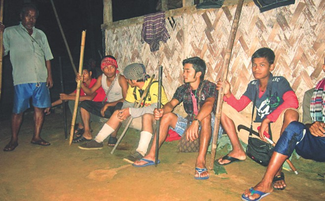 Armed with sticks, male members of the Khasi community guard their houses at Nahar Punjee-1, a hilltop village of the indigenous people, in Moulvibazar's Srimangal upazila on Friday night after Bangalee land grabbers attacked the community earlier in the day in an attempt to evict them. Photo: Mintu Deshwara