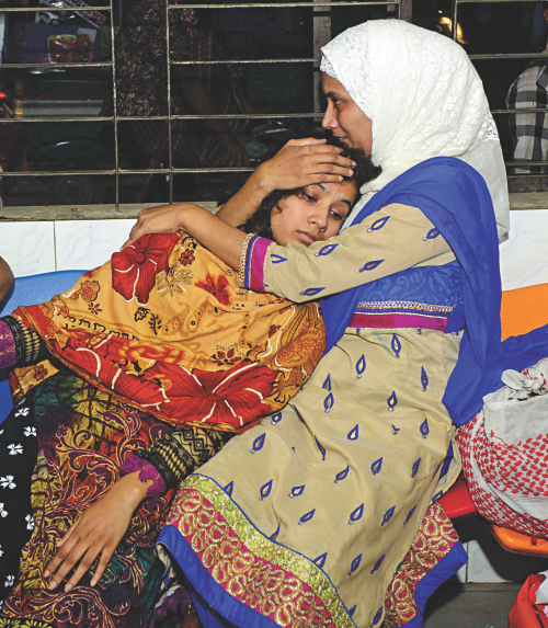 A relative tries to console Ratri, wife of deceased Simon, at Dhaka Medical College Hospital last night. Simon and his father were shot near their Khilgaon home apparently by muggers. Photo: Courtesy