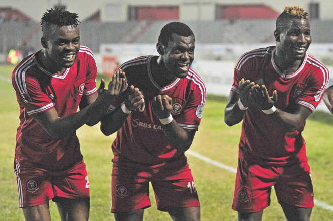 Muktijoddha's Nigerian strikers Eleta Kingsley (C) Nkowcha Kingsley (R) celebrate with compatriot and fellow hitman Sunday Chizoba (L), who became father of his first son on Wednesday, after the latter scored the last goal of his team's 4-2 win over BJMC at the Bangabandhu National Stadium last night. PHOTO: STAR