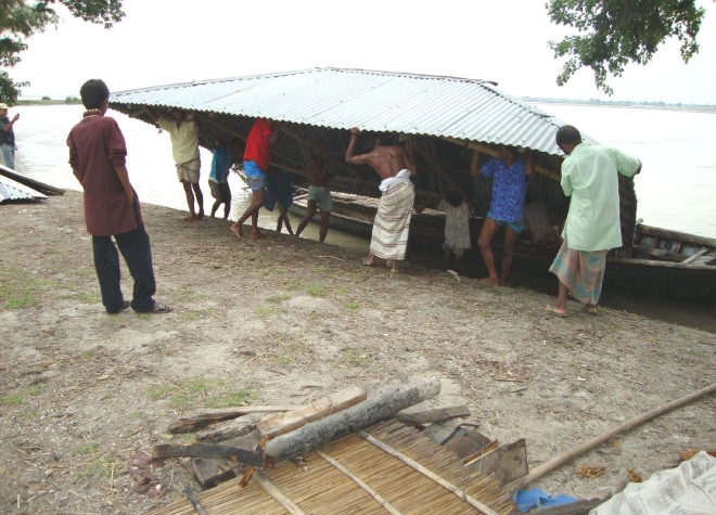 A flood-hit family of Char Dawabari in Hatibandha upazila of Lalmonirhat district puts the corrugated iron roof of their house onto a boat to take it to a safer place. Photo: Star