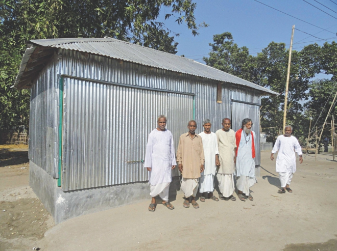 Some of the Hindus, affected during Jamaat-Shibir men's vandalism and looting on October 27 last year, pose in front of a repaired shop at Shafinagar village in Bawra union under Patgram upazila under Lalmonirhat district on Monday. Several other victims, however, are yet to repair their shops and houses, damaged during the attack, for want of money.    PHOTO: STAR