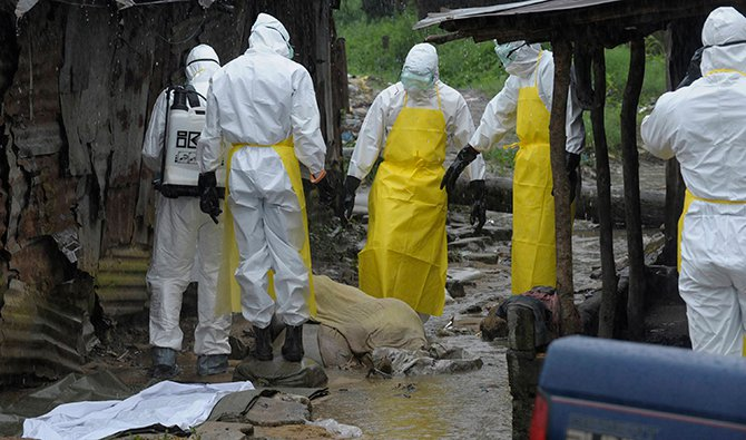 Health workers wearing protective clothing prepare to carry an abandoned dead body presenting with Ebola symptoms at Duwala market in Monrovia. Photo: Reuters