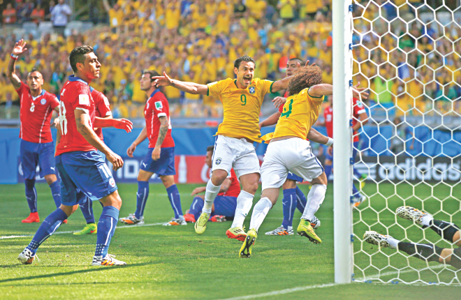 David Luiz (R) starts running for joy after giving Brazil the lead over Chile in the 18th minute in their World Cup Round of 16 game at the Estadio Mineirao in Belo Horizonte on Saturday. Chile however hit back with an equaliser through Alexis Sanchez in the 32nd minute as the first half ended 1-1. PHOTO: REUTERS
