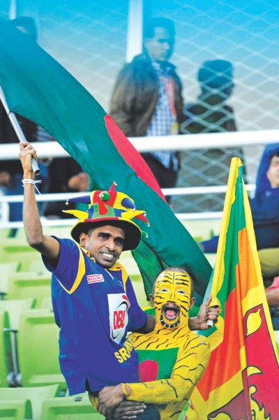 A brilliantly painted Tigers fan lifts a Sri Lankan supporter up at Mirpur yesterday. Ironically, the Tigers on the field also helped out the Lankans to an improbable victory in the 1st  ODI with their poor batting performance. Photo: Firoz Ahmed