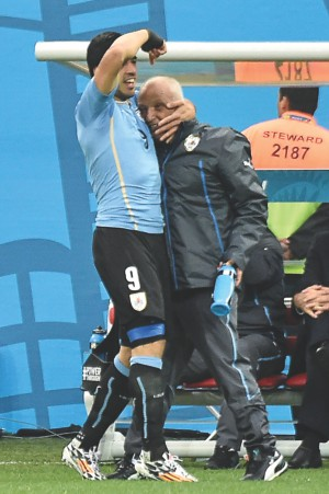 After scoring the opener, Luis Suarez ran straight to the bench and hugged Walter Ferreira, the man who got him fit in less than four weeks after a knee surgery.  PHOTO: AFP