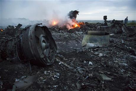 A man walks amongst the debris at the crash site of a passenger plane near the village of Hrabove, Ukraine, Thursday, July 17, 2014. Ukraine said a passenger plane was shot down Thursday as it flew over the country, and both the government and the pro-Russia separatists fighting in the region denied any responsibility for downing the plane. Phot: AP