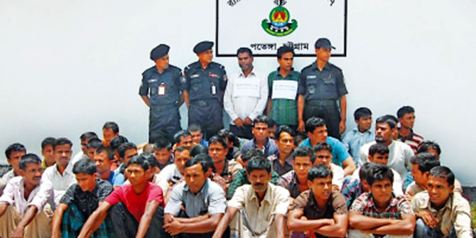 This July, 2012 photo shows 48 men rescued by Rapid Action Battalion while being trafficked to Malaysia through the Bay of Bengal and the two arrested traffickers, standing, in Chittagong.