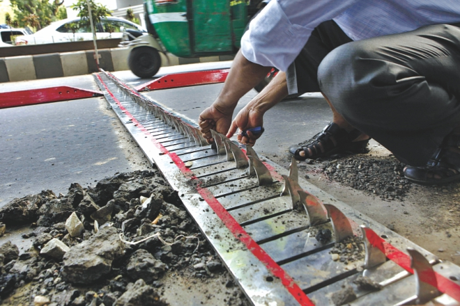 A man fixing the spikes after a number of them stopped retracting. Photo: Anisur Rahman