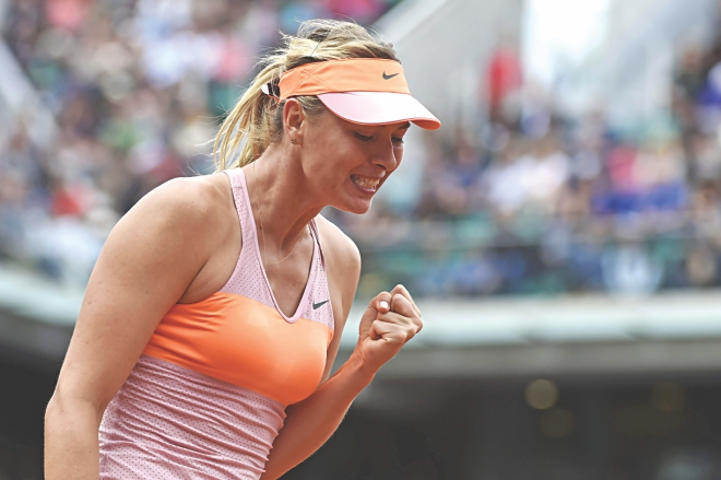 Russia's Maria Sharapova pumps her fist in celebration after beating Spain's Garbine Muguruza in the French Open quarterfinals at the Roland Garros in Paris yesterday. PHOTO: AFP