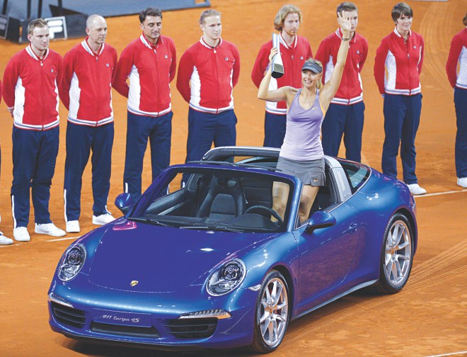 Maria Sharapova holds aloft the Stuttgart Open trophy while standing on the winner's prize, a Porsche 911 Targa sportscar, after the final against Ana Ivanovic yesterday. PHOTO: AFP
