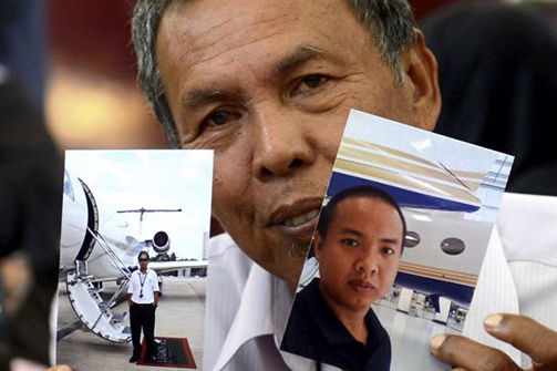 Selamat Omar, showing pictures of his son, flight engineer Mohd Khairul Amri Selamat, who was on board flight MH370. Photo: Bernama