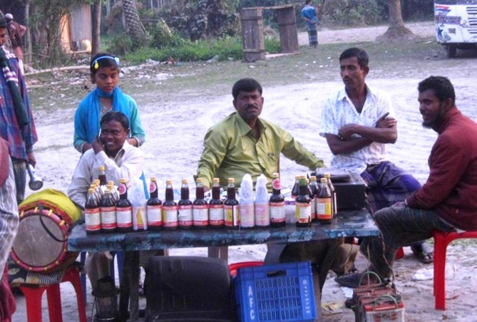 TREATMENT OR CHEATING? ..... Two men sell unauthorised syrup, claiming it to be a panacea, at Dashmina Bazar in Patuakhali, a few days ago. Photo: PHOTO: STAR