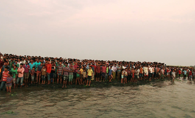 A crowd gathers on the shore of the Meghna at Doulatpur of Gazaria in Munshiganj where a launch went down yesterday afternoon. Photo: Star