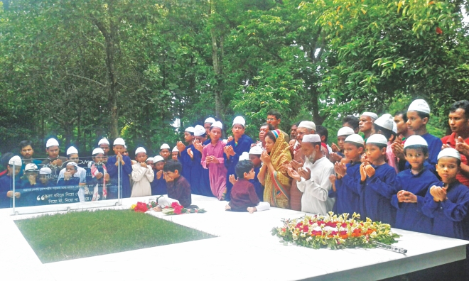 Humayun Ahmed's wife Meher Afroz Shaon and two sons join prayers for his departed soul while fans lay wreaths at his grave in Nuhash Palli on the occasion of his death anniversary yesterday.  Photo: Star