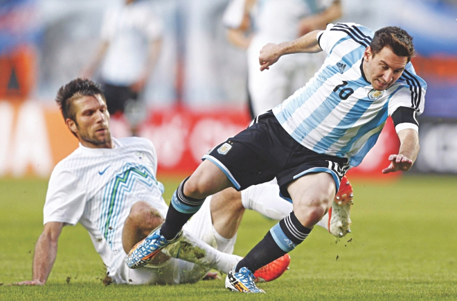 Star Argentina striker Lionel Messi (R) staves off a sliding tackle from Slovenia's Bostjan Cesar during their international friendly in Buenos Aires on Saturday.  PHOTO: AFP