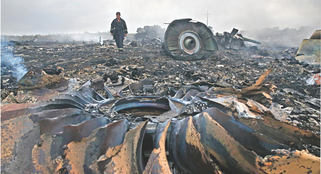 An emergencies ministry member walks at a site of a Malaysia Airlines Boeing 777 plane crash near the settlement of Grabovo in Donetsk region of Ukraine yesterday. Photo: Reuters