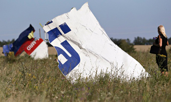 A woman takes a photograph of wreckage at the crash site of Malaysia Airlines flight MH17. Photo: Reuters