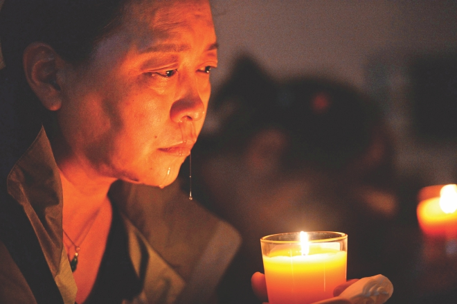 A relative cries while praying for the victims of MH370 in Beijing yesterday. Photo: AFP