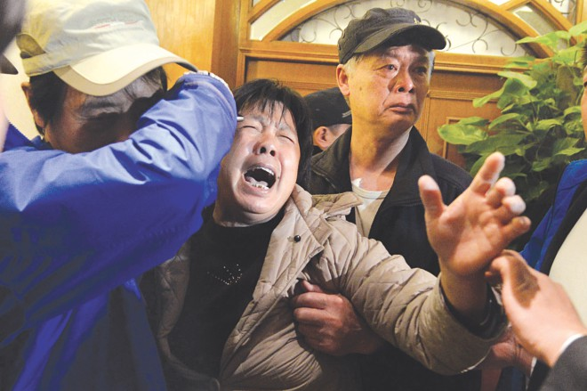 A relative of passengers on Malaysia Airlines flight MH370 cries after hearing yesterday the news that the plane plunged into Indian Ocean. The airline told relatives the plane had been lost and that none on board survived.  PHOTO: AFP
