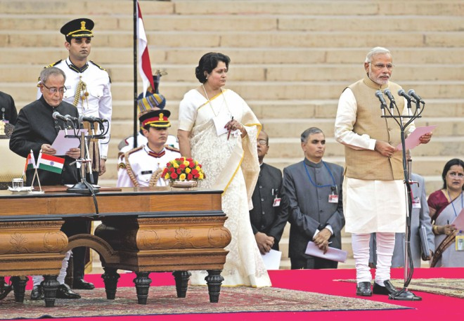 Narendra Modi (R) takes the oath of office as he is sworn in as India's Prime Minister in New Delhi yesterday.  Photo: AFP