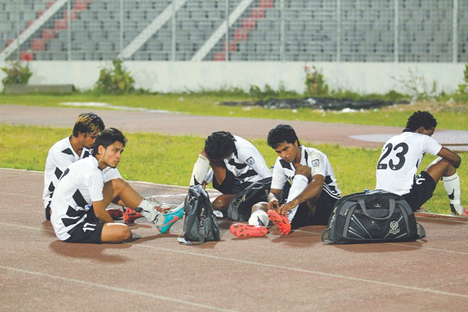 PUSHED TO THE SIDELINES! Dejected Mohammedan players sit on the sidelines of the Bangabandhu National Stadium pitch following their Bangladesh Premier League match against Uttar Baridhara yesterday. PHOTO: STAR