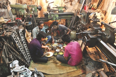 Workers having lunch in a cramped lathe workshop.