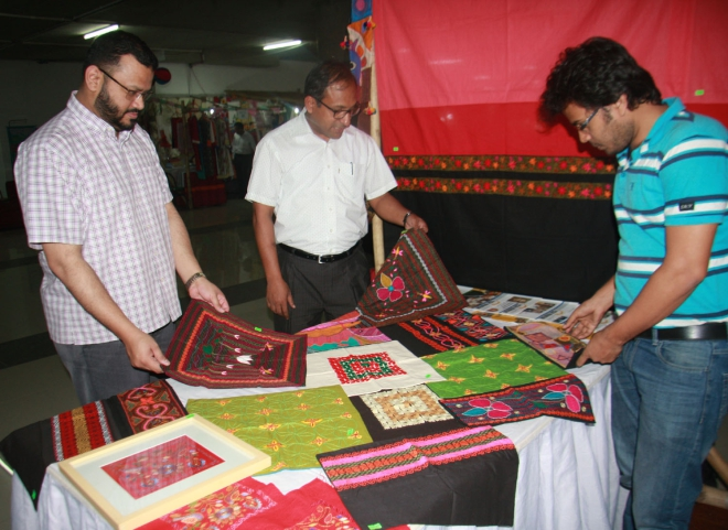Moinuddin Hasan Rashid, managing director of United Group, and Hasibur Rahman, executive director of Management and Resources Development Initiative (MRDI), take a look at products made by vulnerable women who have developed skills under the CSR initiative of MRDI, in the Unimart Baishakhi fair in the capital. Photo: MRDI