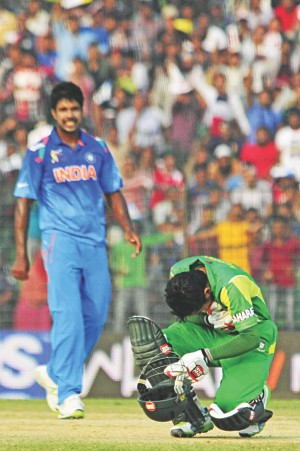 Mushfiqur Rahim is in agony after being struck on the chest by a Varun Aaron (L) beamer at Fatullah yesterday. Photo: Star